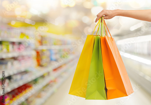 Photo Stands hand with shopping bags over supermarket