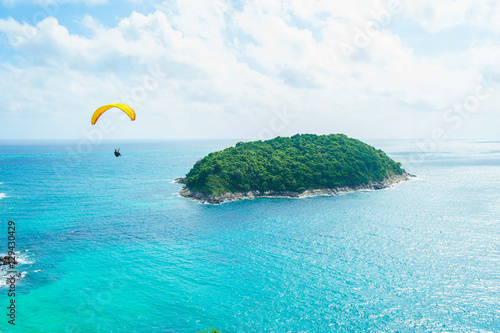 Foto op Plexiglas Luchtsport Skydiver flying over the water with island. Paragliding concept.