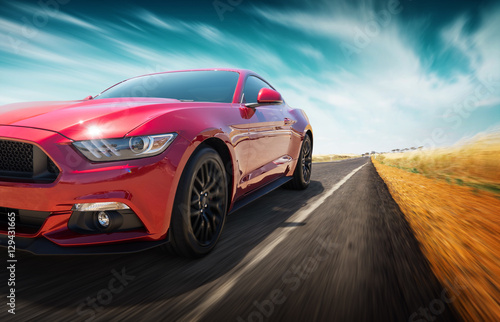 Sport car fast speed driving on the apshalt road at field of golden wheat background . - 129431665