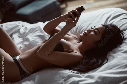 Fotografia  Portrait of a beautiful sensual asian woman with phone