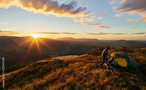 Fotobehang Kamperen A hiker camping on the mountain summit of Place Fell in the Lake District. UK