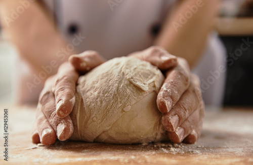 Fotografie, Obraz  Close-up of chef hands kneading raw bread dough on wooden board