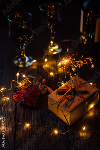 christmas present with sparkler christmas lights and two glasses of wine on brown wooden table