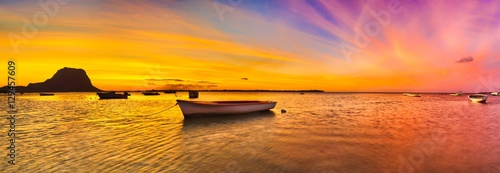 Spoed Foto op Canvas Koraal Fishing boat at sunset time. Le Morn Brabant on background. Pano