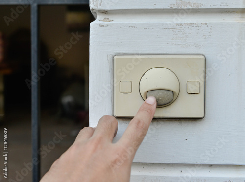 фотографія  Human hand push the doorbell at the front home