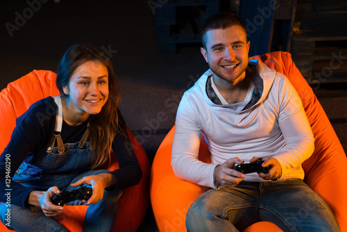 Two young gamer sitting on poufs and playing video games togethe Poster