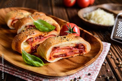 Photo  Traditional Italian Stromboli stuffed with cheese, salami, green onion and tomat