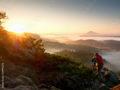 Foto op Canvas Diepbruine Happy photo enthusiast enjoy photography of fall daybreak in nature on cliff
