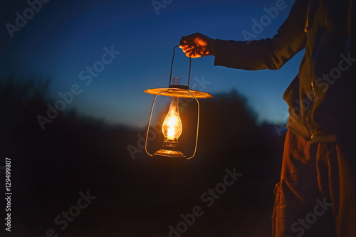 Photo  man holding the old lamp with a candle outdoors