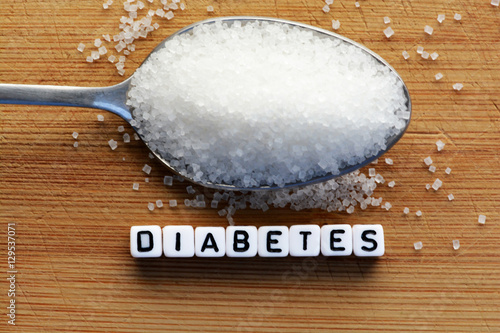 Fotografía  Diabetes block letters in crossword and sugar pile on a spoon