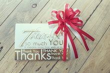 Red Ribbon Bow On Wooden Board With Thank You Card