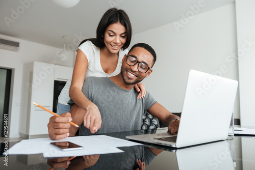 Fotografía  Loving young couple using laptop and analyzing their finances