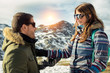 Young couple enjoying vacations in Asturias Somiedo natural park at a snowy mountain beautiful landscape on a sunny day. Man and woman smiling cheerfully looking each other with cool sun glasses.