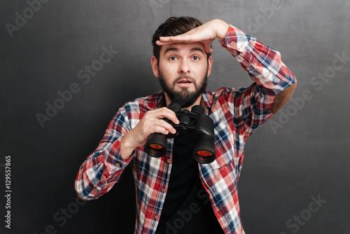 Man in plaid shirt holding binoculars and looking far away