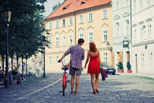 Couple In Red Walking On The Street With Bike In Old Town In Pra