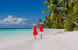 happy loving couple walking on tropical beach