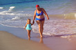 grandmother with little girl go swim at beach