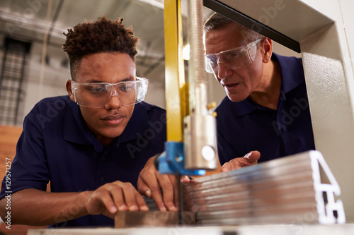 Photo Carpenter Training Male Apprentice To Use Mechanized Saw