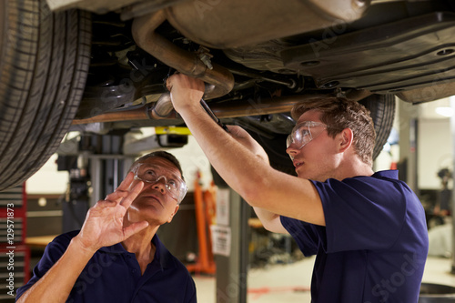 Mechanic And Male Trainee Working Underneath Car Together