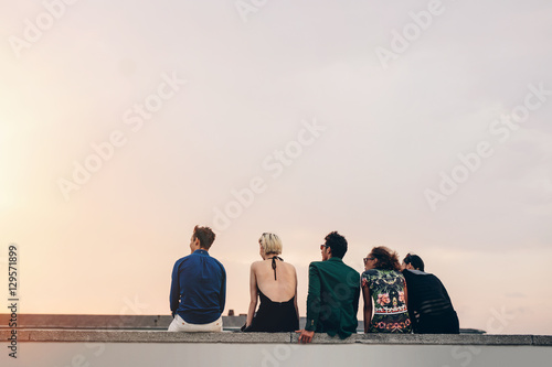 Fotomural Friends sitting together on rooftop at sunset