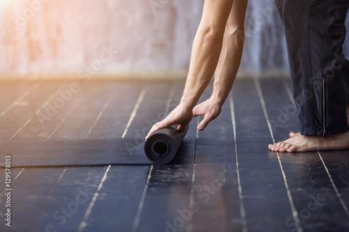 Staande foto School de yoga Woman rolling her mat after a yoga class