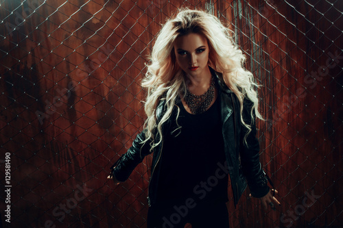 rock-n-roll-girl-young-beautiful-woman-dances-in-dark-alley-against-the-fence-mesh