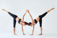 Two Young Women Doing Yoga Asa...