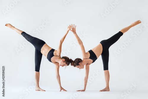 Fotografie, Obraz  Two young women doing yoga asana Ardha Chandrasana