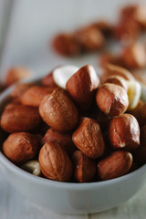 Dry peanuts in white bowl over the white table