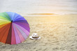 Hat, sunglasses and rainbow colored umbrella on a tropical beach