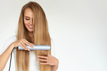Hairdressing. Woman With Beautiful Long Hair Using Straightener