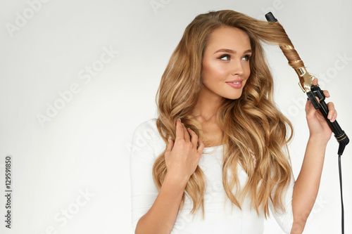 Photo Curly Hair. Beautiful Woman Curling Long Wavy Hair With Iron