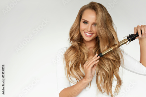 Curly Hair. Beautiful Woman Curling Long Wavy Hair With Iron Wallpaper Mural