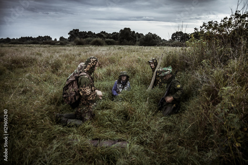 Foto op Aluminium Jacht Hunting scene with group of hunters in rural field with dramatic sky in expectation of hunting in tall grass during hunting season