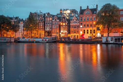Photo  Amsterdam canal Amstel with typical dutch houses and boats during twilight blue hour, Holland, Netherlands