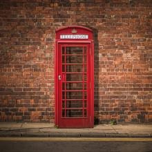 British Phone Box Against Red Brick Wall
