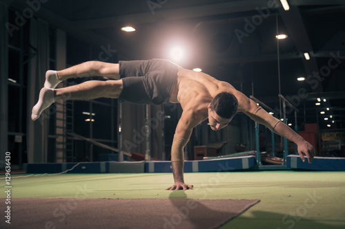 Keuken foto achterwand Gymnastiek Young man gymnast, one hand cartwheel