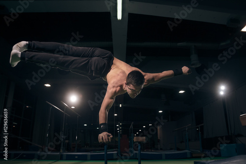 Spoed Foto op Canvas Gymnastiek Young man one hand cartwheel