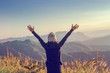 Carefree Happy Woman Enjoying Nature on grass meadow on top of mountain cliff with sunrise. Beauty Girl Outdoor. Freedom concept.
