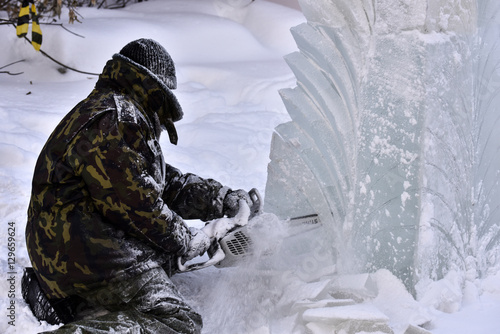 Foto  Worker using a chainsaw carving an ice sculpture
