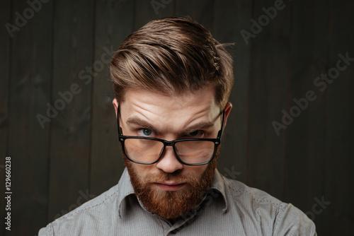 Fotografie, Obraz  Young bearded man in eyeglasses staring at camera
