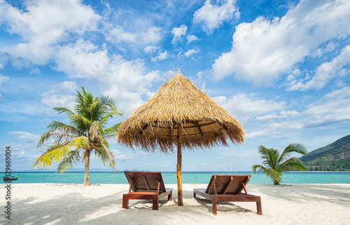 Poster Zanzibar Vacation in tropical countries. Beach chairs, umbrella and palms on the beach.