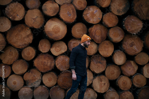 Young man walks by lumber stockpile - 129669478