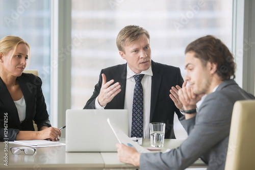 Furious boss scolding young frustrated intern with bad work results Wallpaper Mural