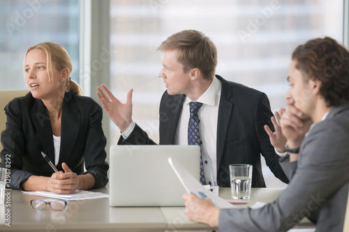 Furious boss scolding young frustrated interns with bad work results Canvas Print