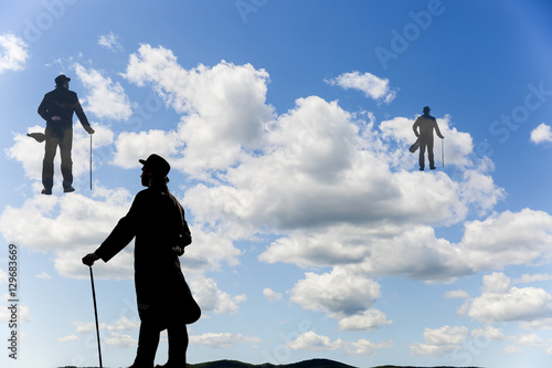 Photo  Surrealistic image of silhouettes of men with a cane and bowl hat climbing up th