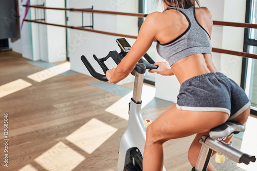 Fotografie, Obraz  Muscular young woman working out on the exercise bike at the gym, intense cardio workout