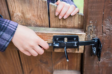 Young Woman Opening Lock On Wooden Door