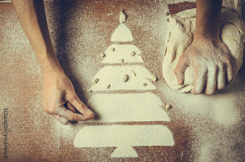 Female hands pressing dough and make the Christmas cookies
