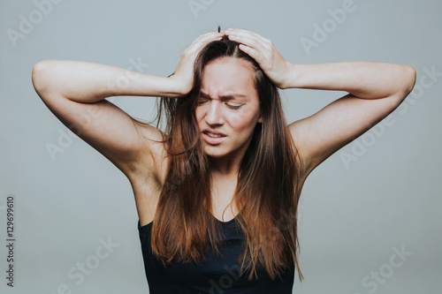 Photo Studio shot of young pretty woman falling into despair and clutching her head isolated on grey background